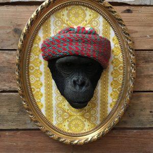 Tête de singe coiffée d'un bonnet rouge et encadrée